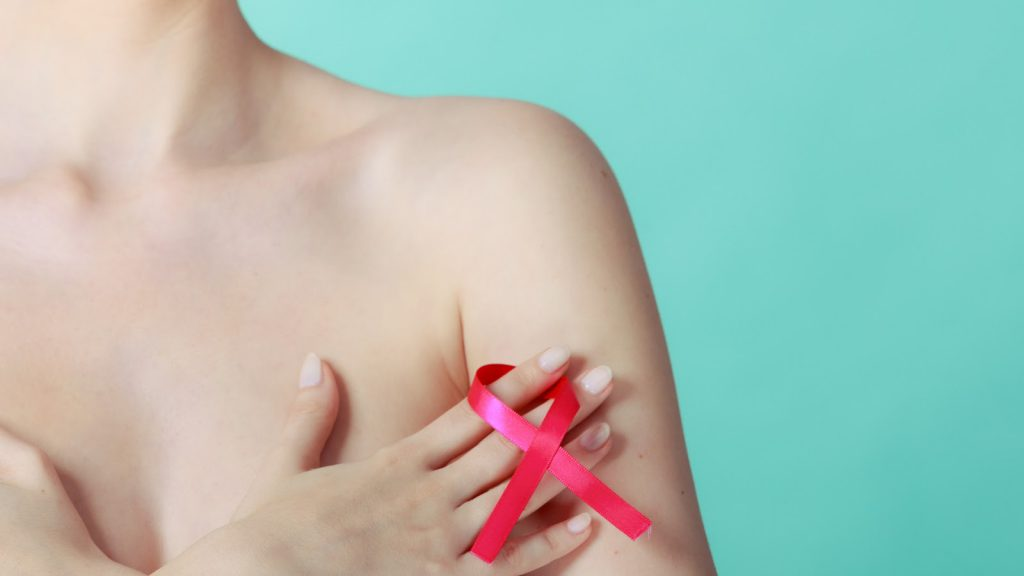Health care, medicine and breast cancer awareness concept. Young naked woman with pink ribbon symbol covering her chest, on blue