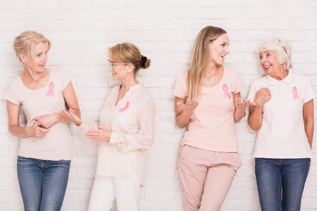 Women wearing pink against cancer standing beside white wall