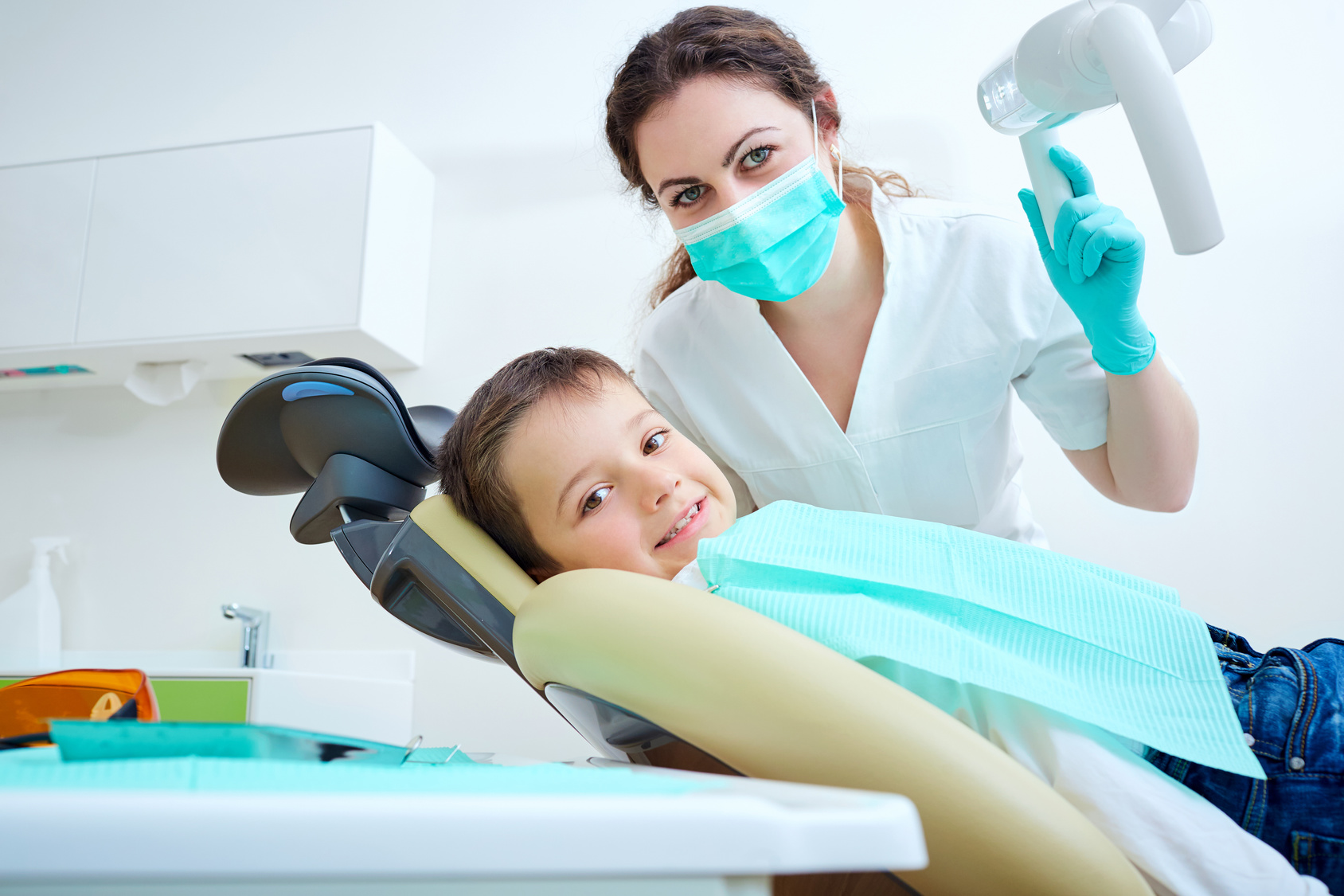 Beautiful kid boy smiling in dentist's chair the office treats teeth. Doctor mask and baby looks at camera.