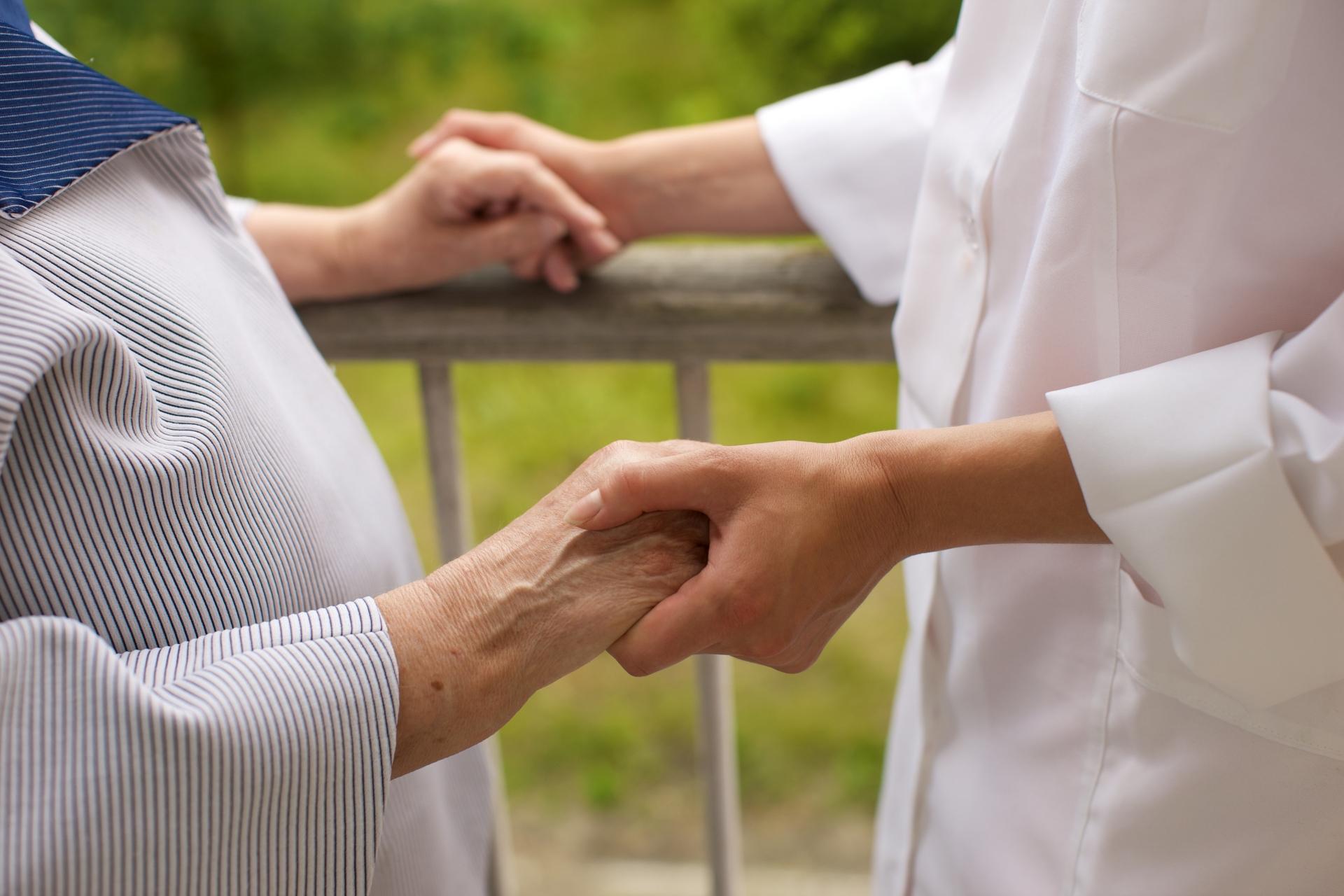 患者と手を取り合う