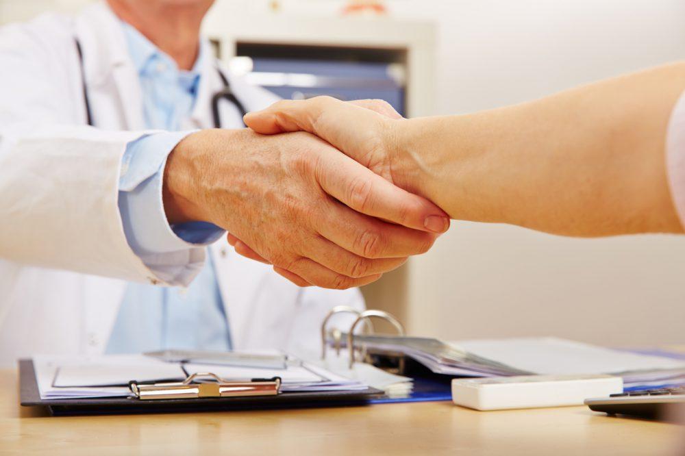 Patient beim Händeschütteln beim Arzt in der Praxis