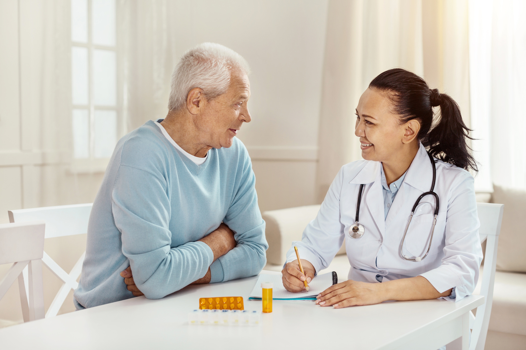 Delighted cheerful doctor sitting together with her patient