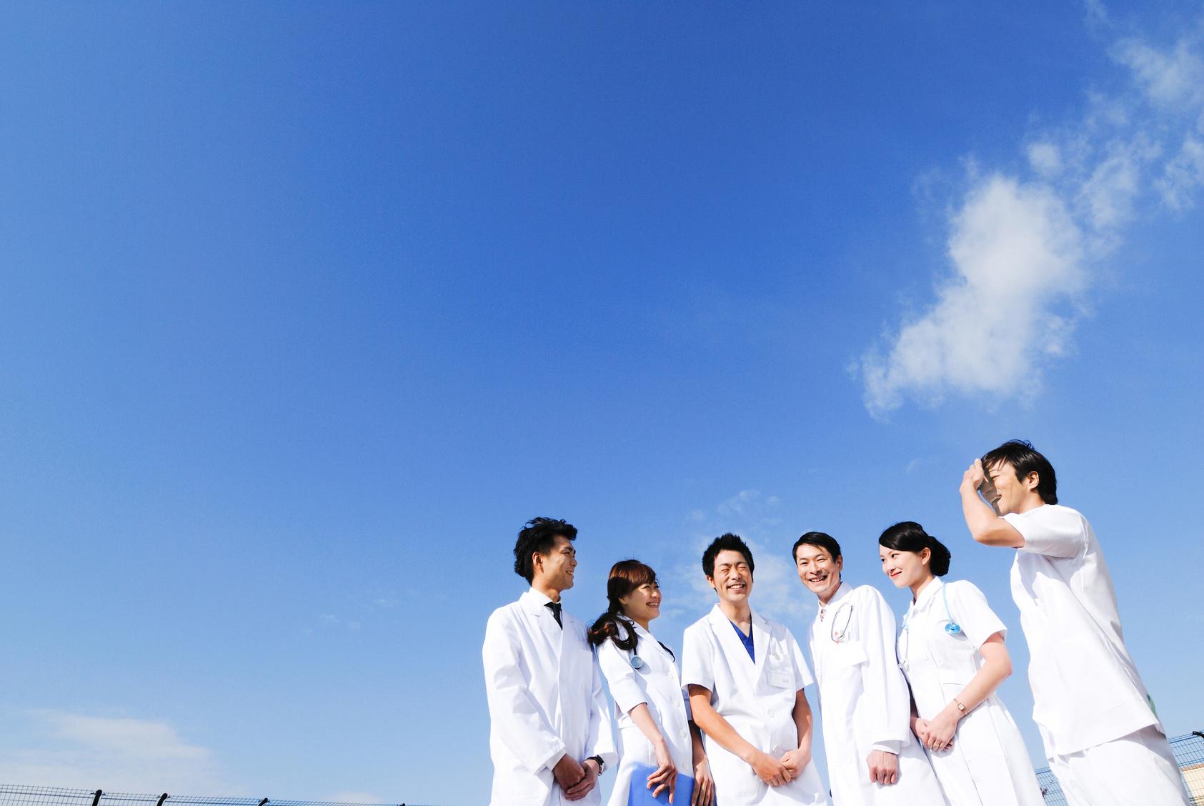 青空を背景に立つ医師・看護師