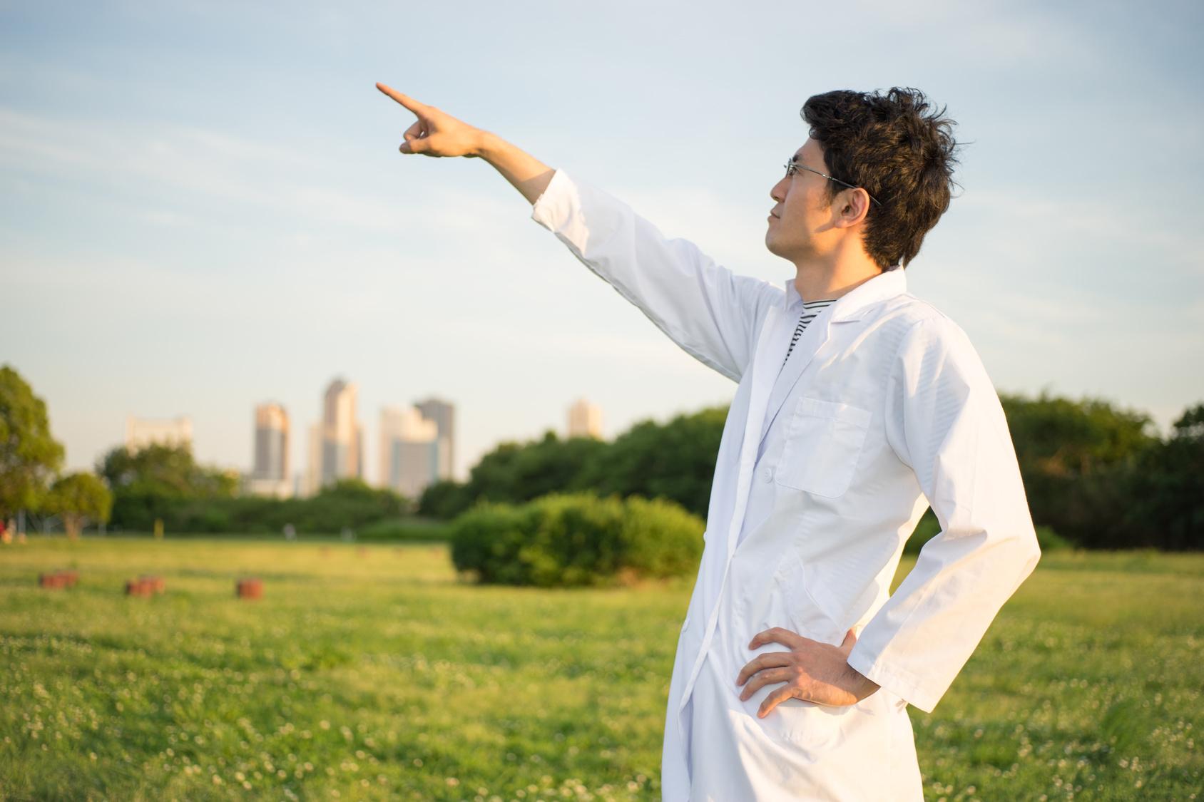 白衣姿の男性(ビル群・公園・芝生)