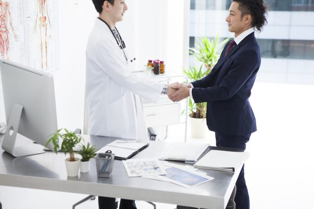 Doctor and salesman of pharmaceutical company are shaking hands