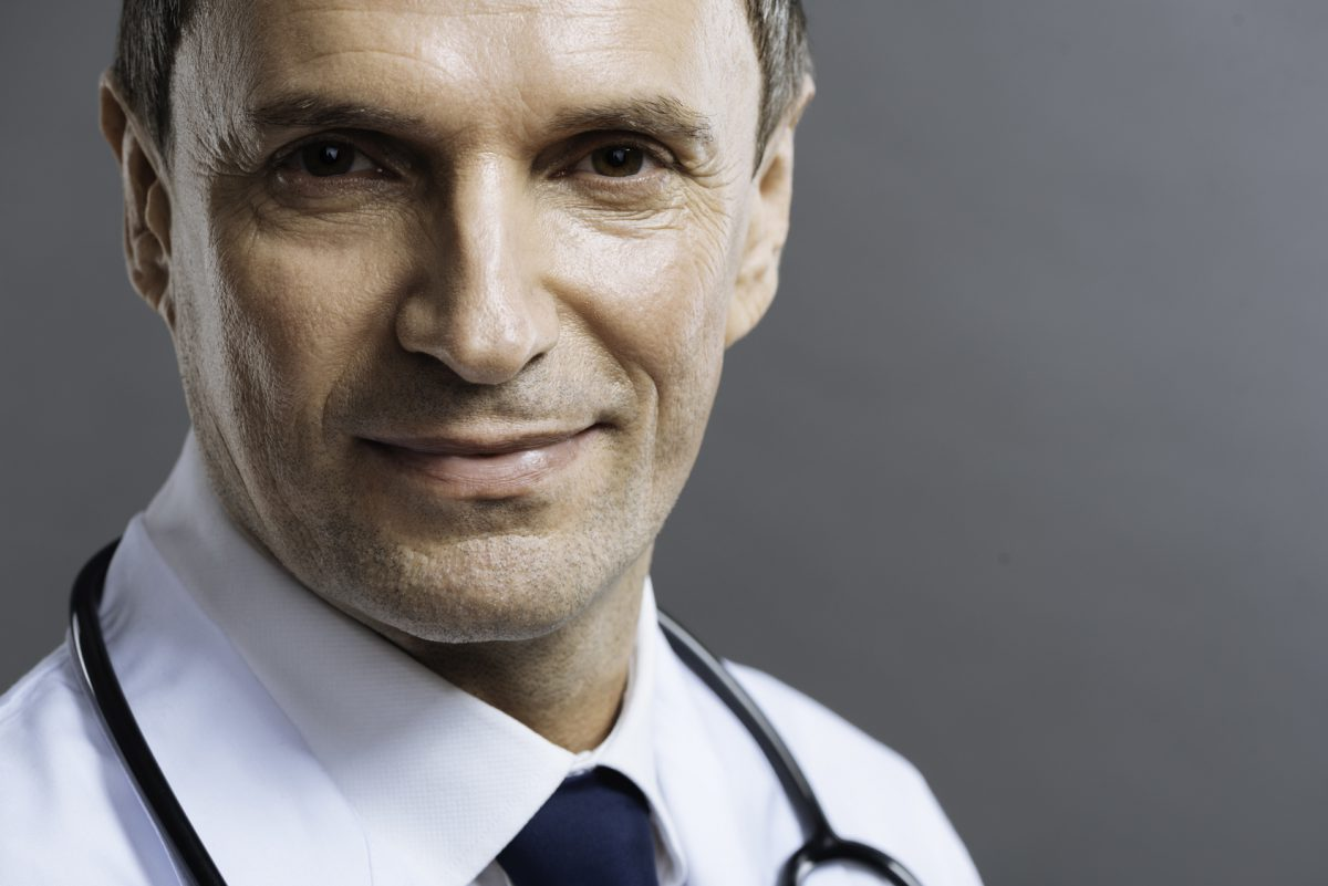 Portrait of handsome doctor smiling on a grey background