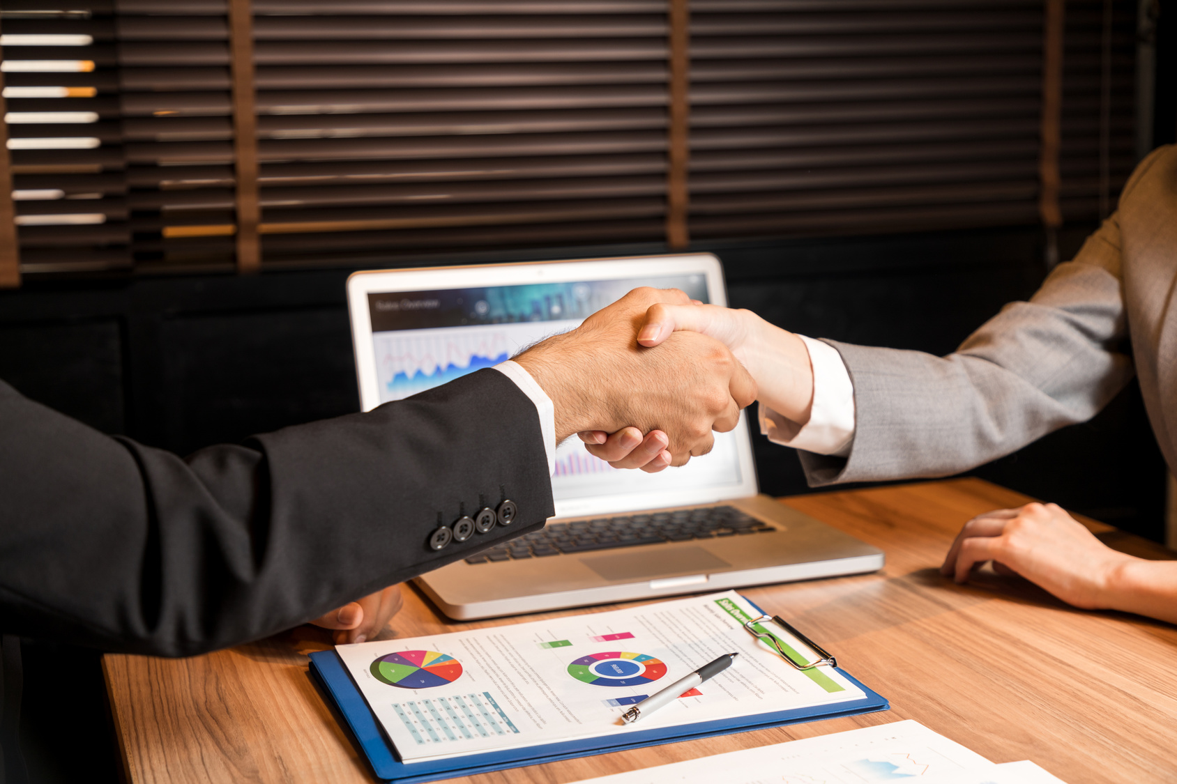 business persons shaking hands.