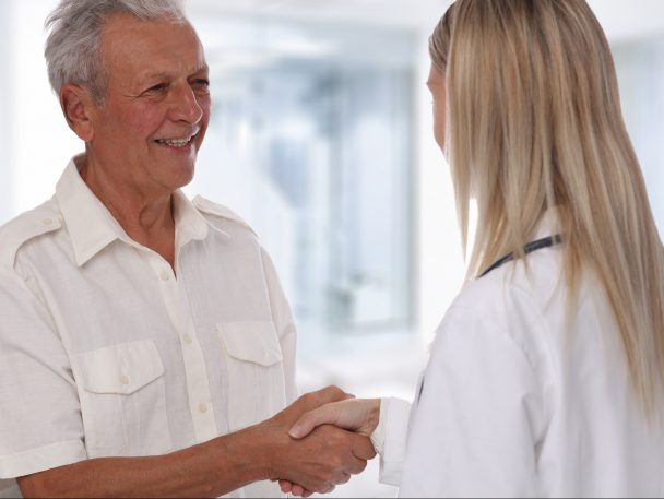 Smiling female doctor giving handshake to senior male patient. Healthcare concept