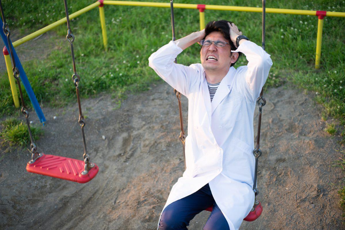 公園で苦悩する白衣の男性