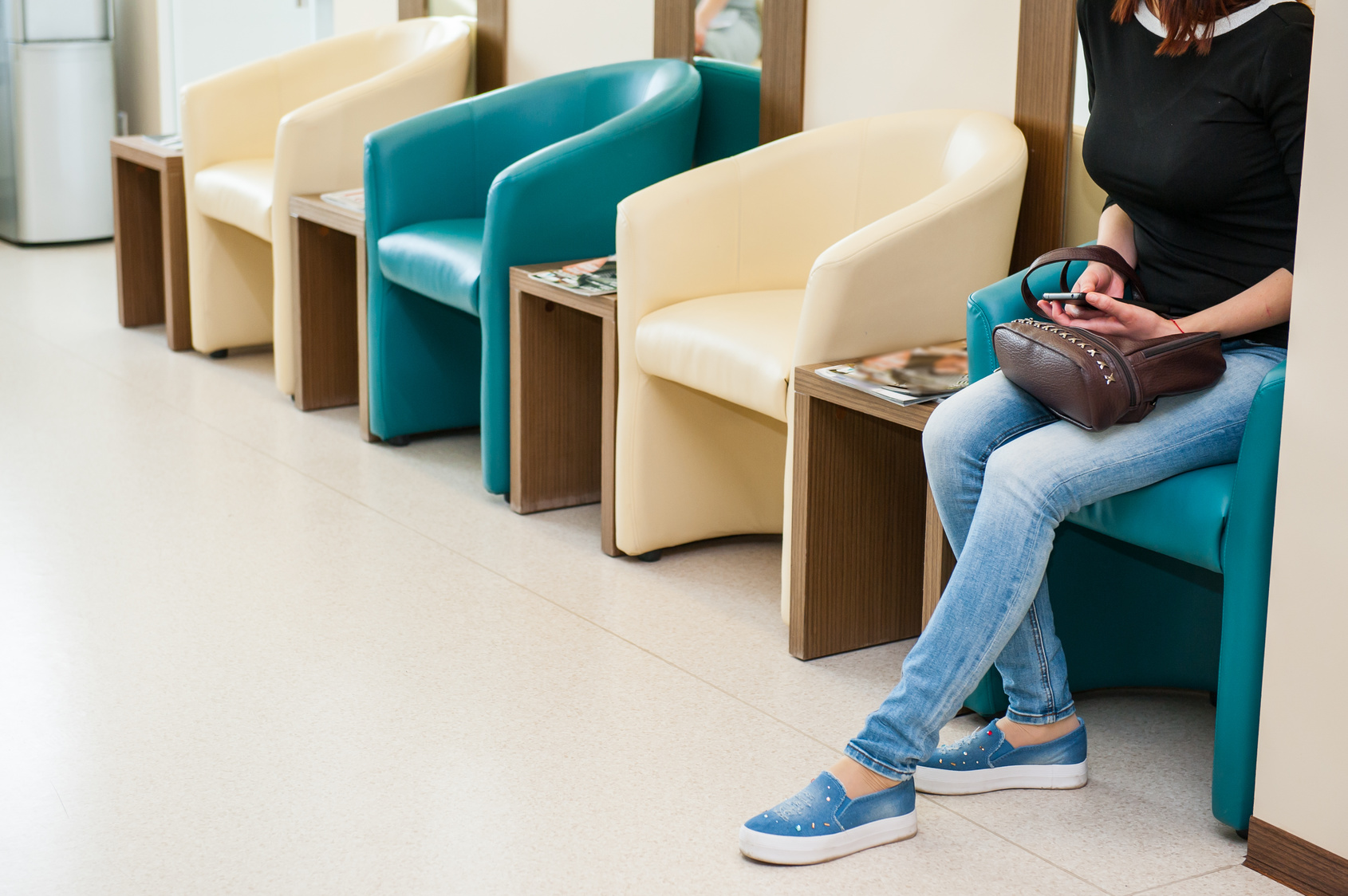 Young girl sitting in waiting room on the one of row of blue and ivory chairs in hall. Selective focus. Medicine, business concept