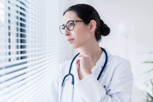 Young female doctor daydreaming while looking through the window