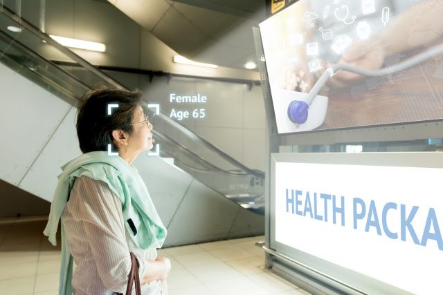Intelligent Digital Signage marketing and face recognition concept. Old woman watch artificial intelligence digital advertisement about healthcare package in shopping Mall.