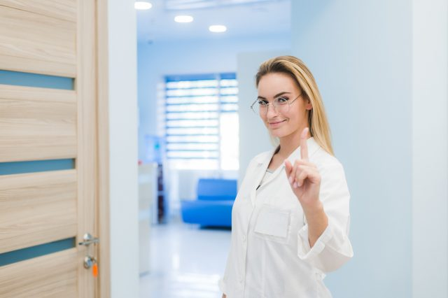 Medical doctor woman smile, nurse wear white surgery suit, point finger up, concept of advertisement product, empty copy space.Over hospital interior