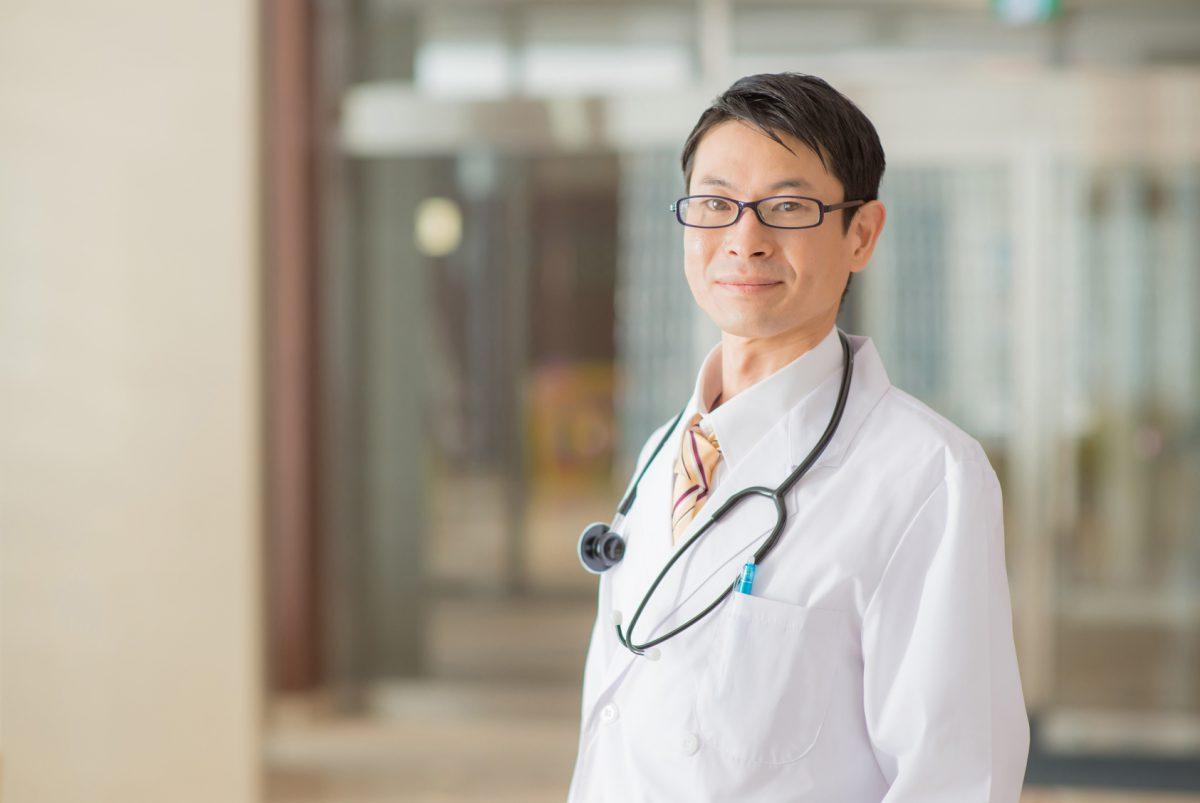 病院内に立つ白衣の男性医師