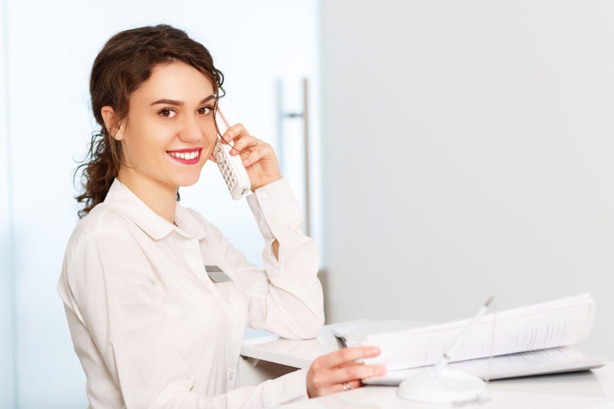 friendly woman behind reception desk administrator