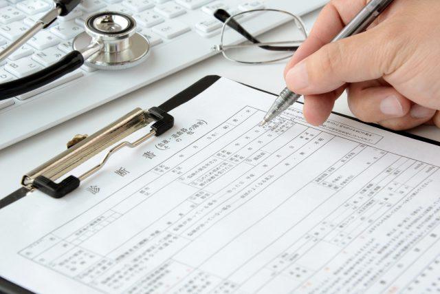 診断書を書こうとする医師