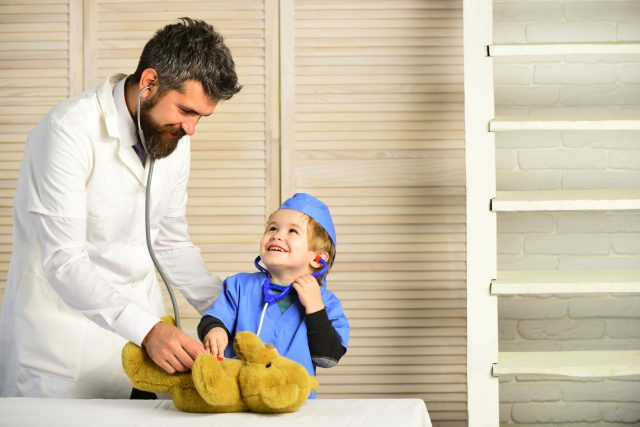 Man with beard and boy hold stethoscope on wooden background