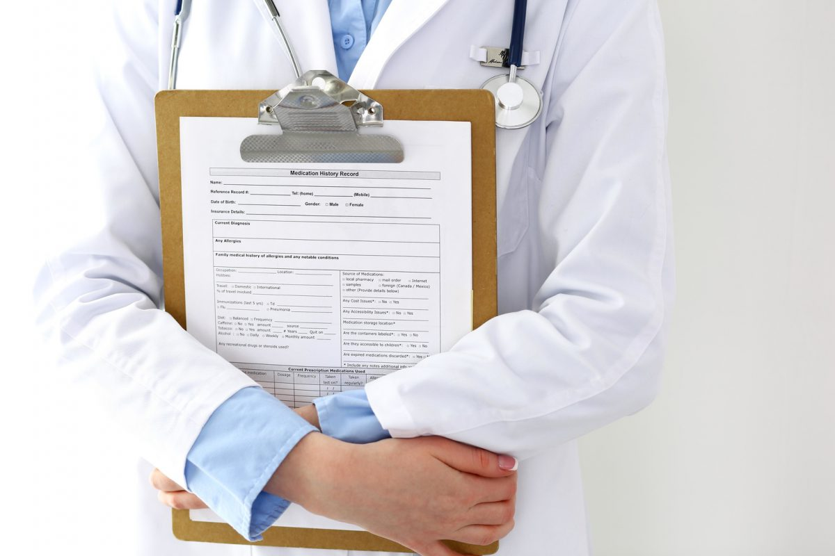 Female doctor filling up medical form on clipboard closeup.  Physician finishing up examining his patient in hospital and ready to give a prescription to help. Healthcare, insurance and medicine concept.