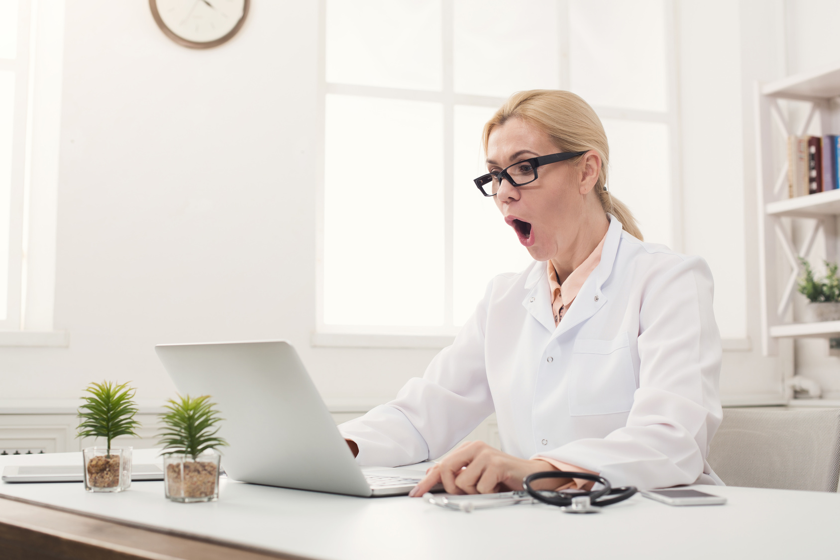 Shocked doctor looking at laptop