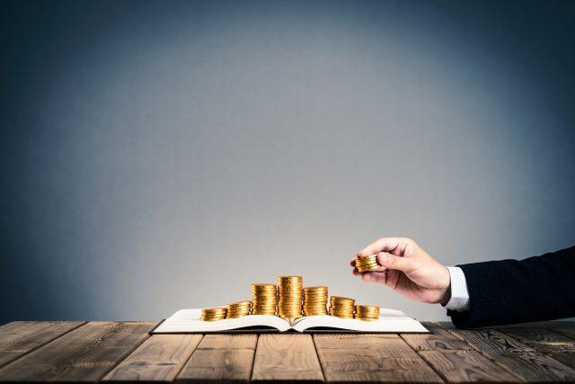 お金を積み上げるビジネスマンの手
