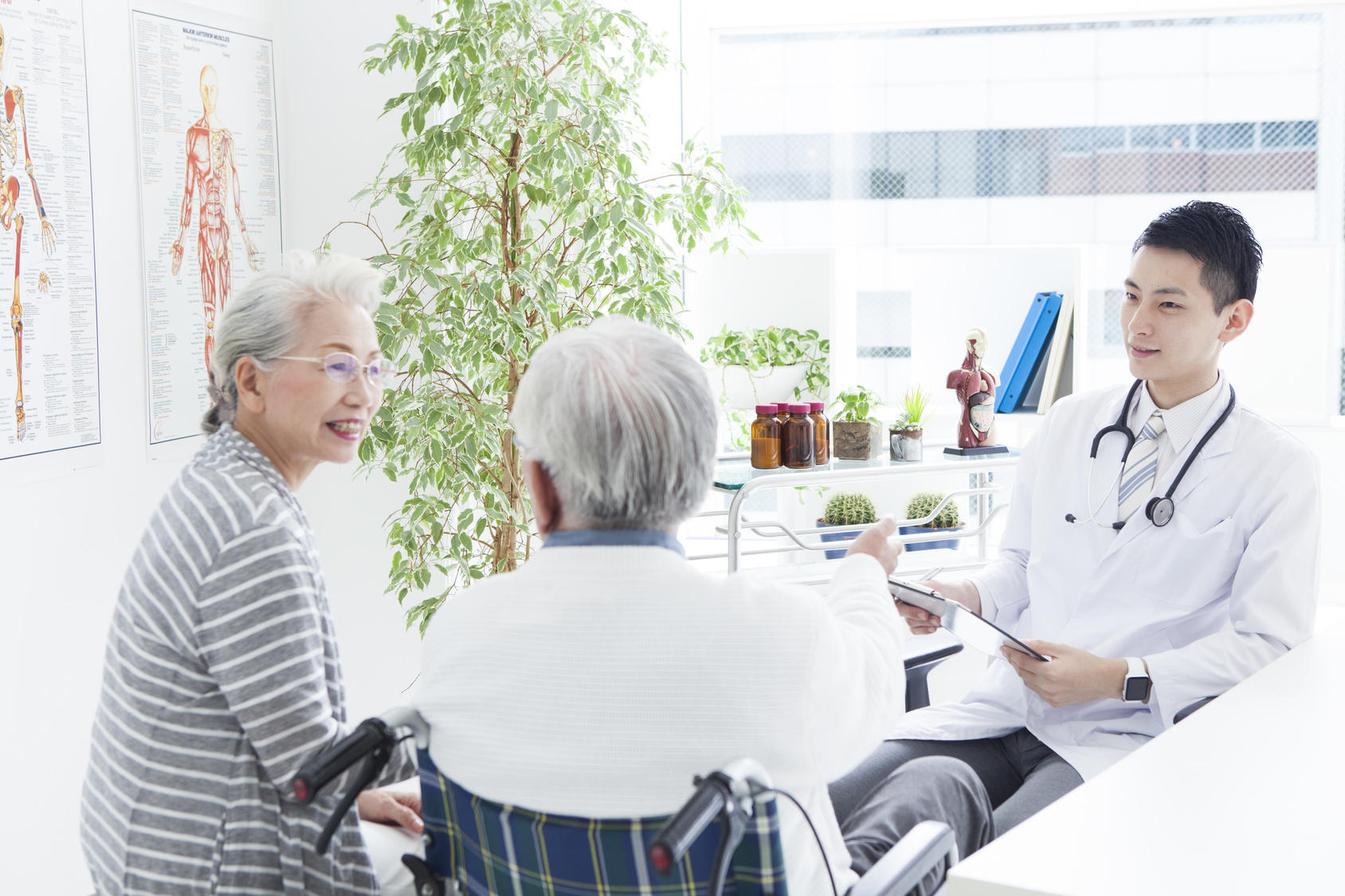 A young doctor and an elderly patient have a happy conversation