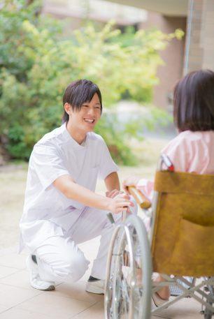 車椅子の女性患者に微笑みかける男性看護師
