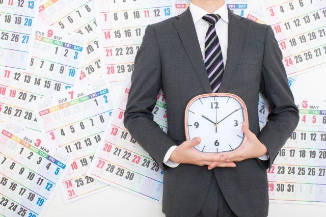 カレンダーの前で時計を持っているビジネスマン