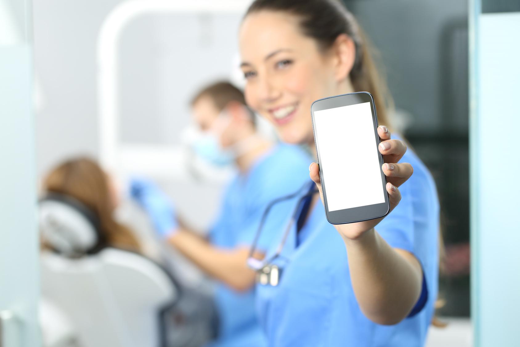 Female dentist showing phone screen