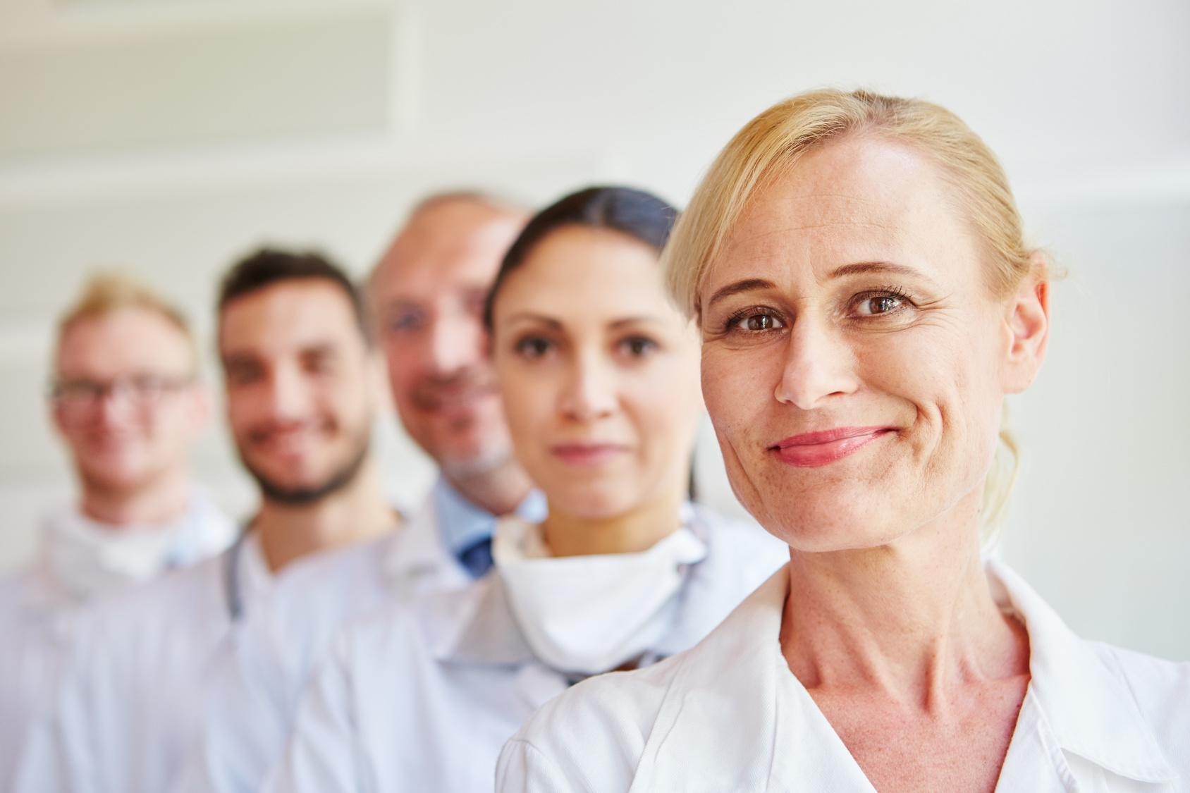 Frau als Ärztin mit Ärzteteam
