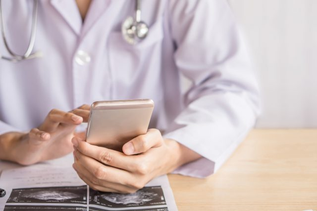 doctor hand using smart phone while working at hospital