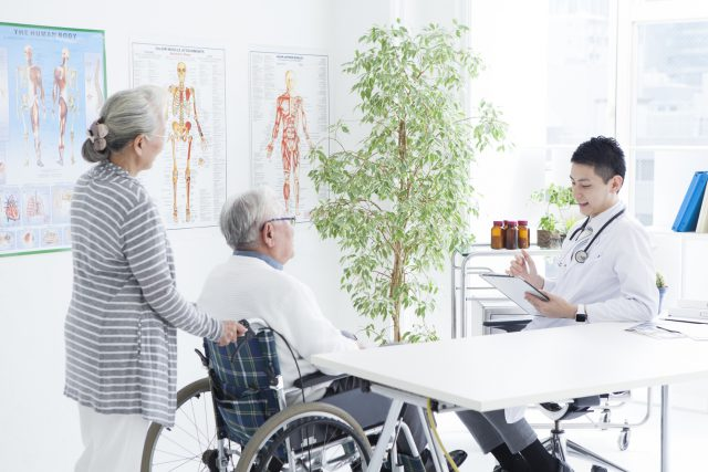 A young doctor is talking with an elderly couple