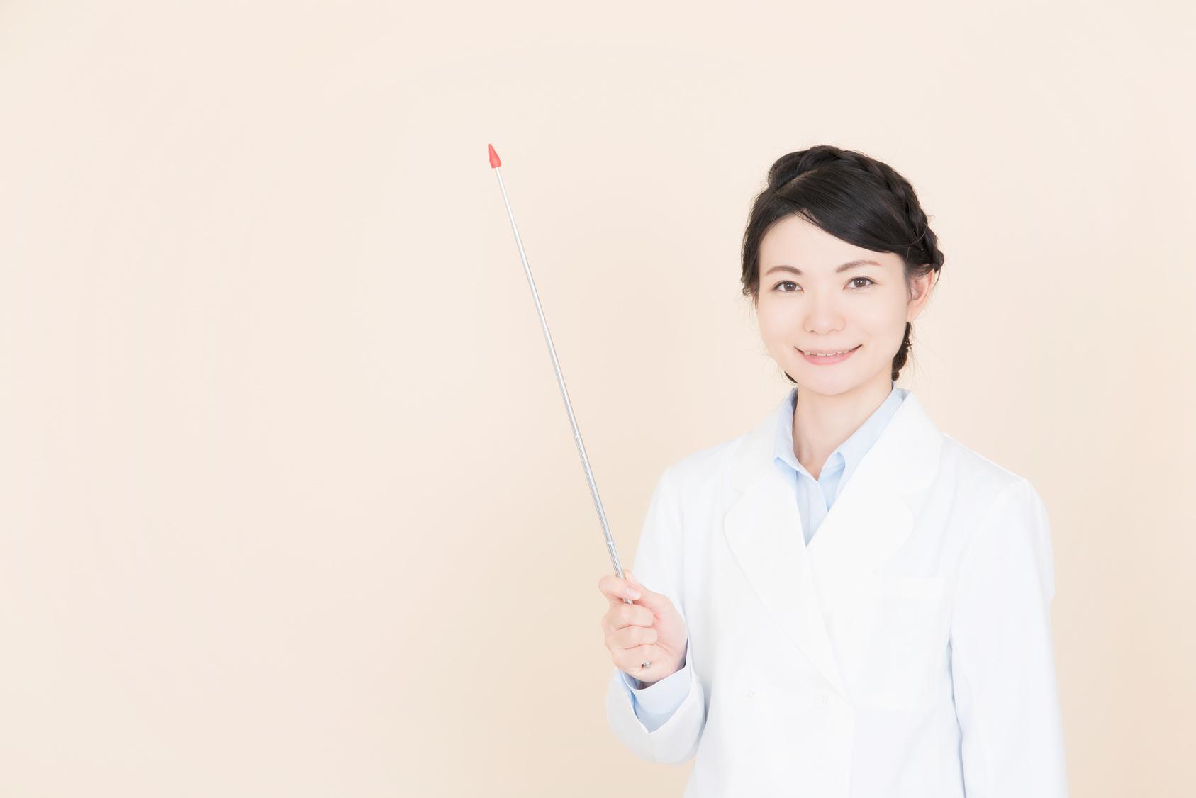 指し棒を持つ白衣の女性
