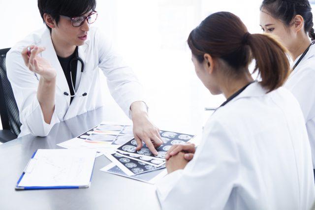 若手医師たちが資料を見ながら打ち合わせをしている