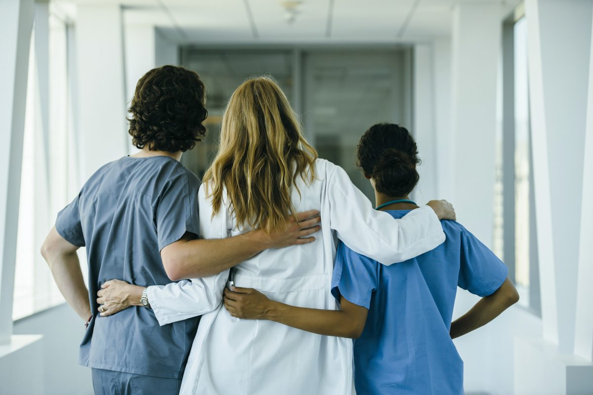 Doctor and nurses hugging