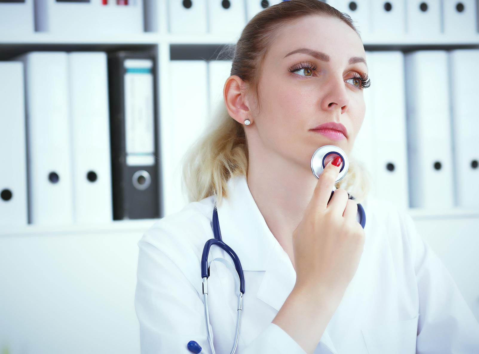 Mused female doctor holding her hand with stethoscope near her chin while looking into the distance.