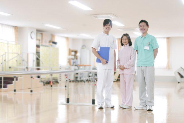 リハビリ室に立つ患者と男性理学療法士と男性看護師