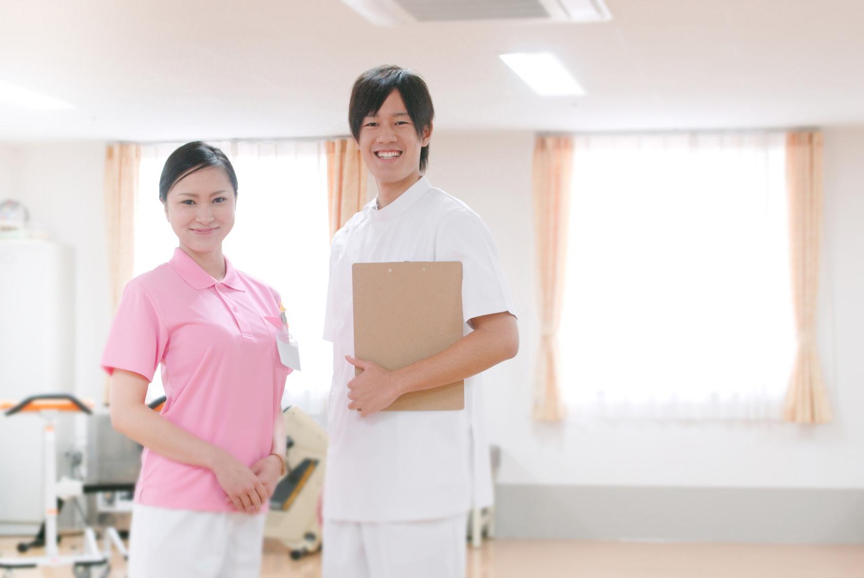 リハビリ室に立つ女性理学療法士と男性看護師