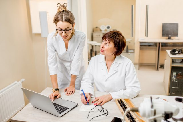 Senior woman ophthalmologist with young female assistant in the office