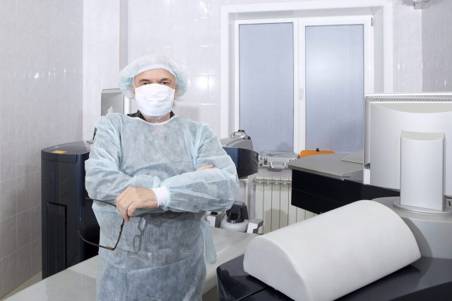A male surgeon is standing near the operating table before the beginning of an operation for vision correction