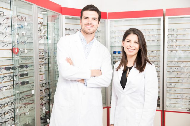 Attractive opticians standing in store smiling looking at camera