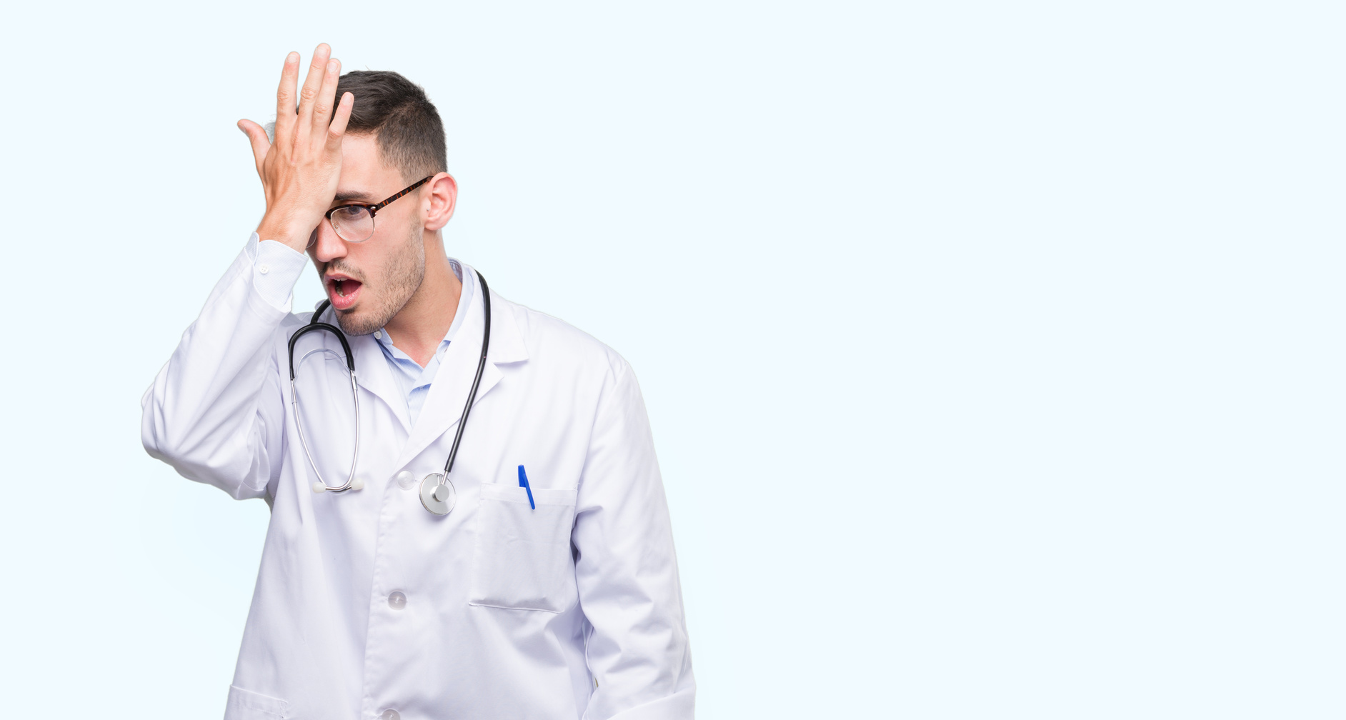 Handsome young doctor man surprised with hand on head for mistake, remember error. Forgot, bad memory concept.