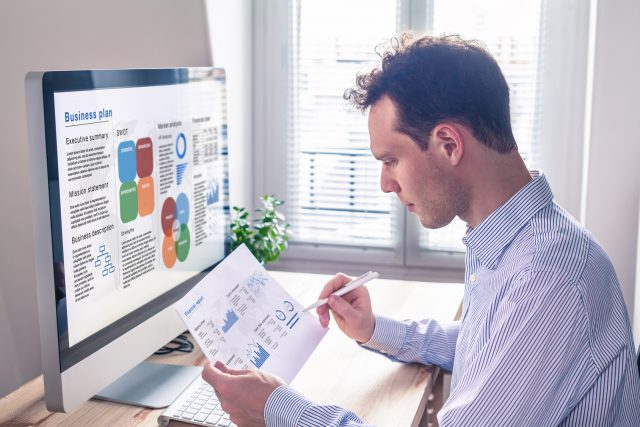 Businessman working on business plan on computer screen in office